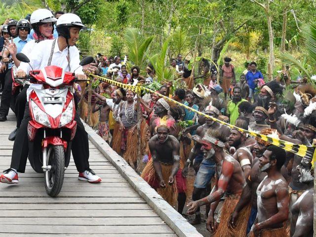 Saat Presiden Jokowi dan Ibu Iriana Berboncengan Naik Motor Listrik di Asmat